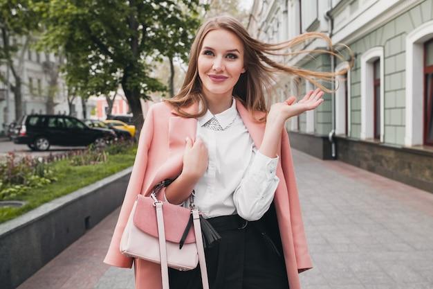 Szczęśliwa atrakcyjna stylowa uśmiechnięta kobieta spaceru ulicą miasta w różowym płaszczu wiosenny trend w modzie trzyma torebkę, elegancki styl, macha długimi włosami
