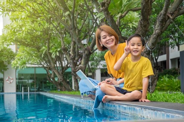 Szczęśliwa azjata matka, syn używa laptop przy outdoors pływackim basenem i