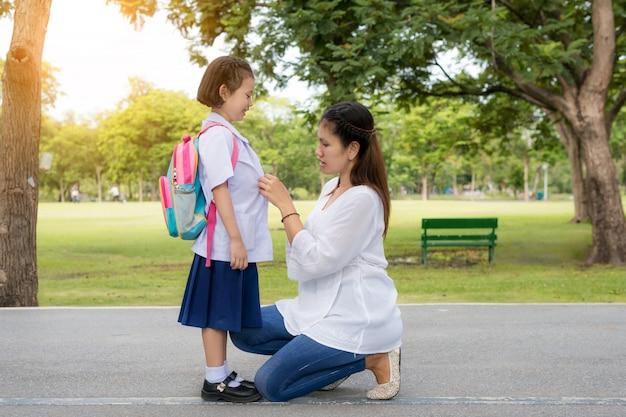 Szczęśliwa azjata matka z dzieciaka uczniem w szkole.
