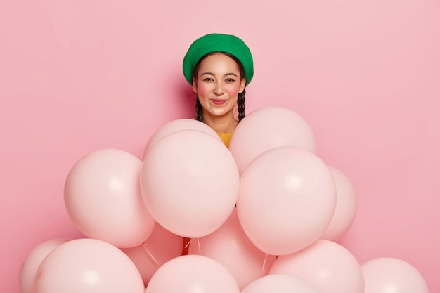 Szczęśliwa azjatka nosi modny zielony beret, przychodzi na wesołe przyjęcie, stoi za balonami z helem