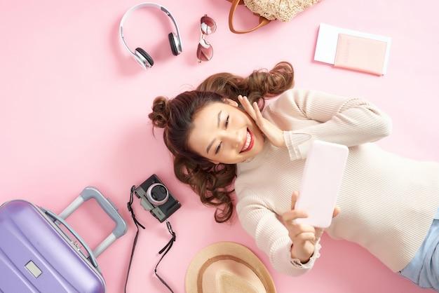 Szczęśliwa azjatka używająca telefonu do robienia zdjęć i leżąca na różowej podłodze z bagażem podróżnym