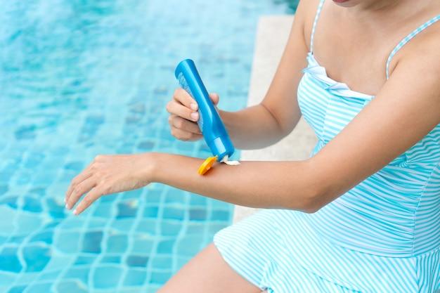 Szczęśliwa azjatka w jednoczęściowym stroju kąpielowym nakładająca krem do opalania na jej han. ochrona przed poparzeniem słonecznym.