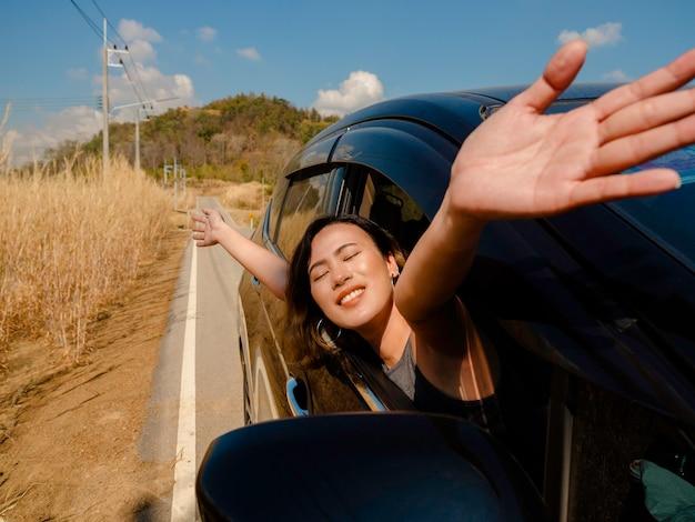 Szczęśliwa Azjatka Z Krótkimi Włosami, Zamykając Oczy I Podnosząc Ręce, Czując Wolność Podczas Podróży Samochodem. Atrakcyjne Podróżujące Kobiety Cieszą Się I Uśmiechają Na Widok Na Zewnątrz Samochodu, Na Drodze. Premium Zdjęcia