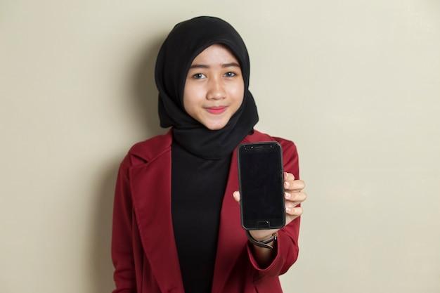 Szczęśliwa azjatycka biznesowa kobieta w hidżabie, wykazując telefon komórkowy. portret uśmiechnięta kobieta, pozowanie