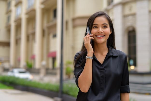 Szczęśliwa azjatycka bizneswoman na zewnątrz na ulicy miasta rozmawia przez telefon, uśmiechając się i spacerując