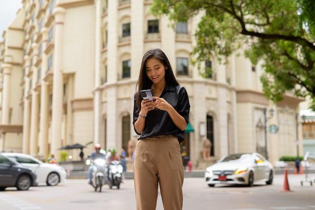 Szczęśliwa azjatycka bizneswoman na zewnątrz na ulicy miasta za pomocą telefonu komórkowego podczas wysyłania sms-ów