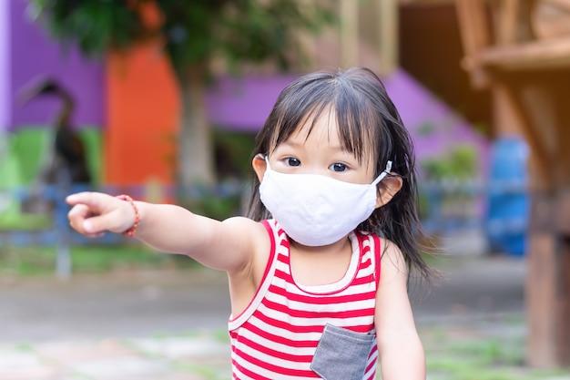 Szczęśliwa azjatycka dziecko dziewczyna uśmiecha się tkaniny maskę i jest ubranym. wskazuje palcem na plac zabaw.