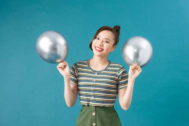 Szczęśliwa azjatycka dziewczyna bawi się srebrnymi balonami