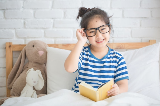 Szczęśliwa azjatycka dziewczyna czyta opowieści książkę na łóżku