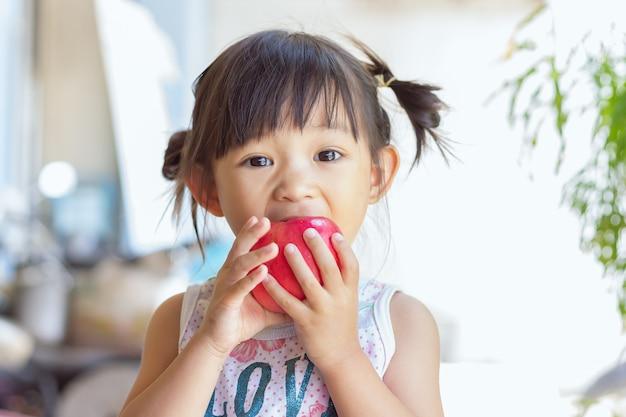 Szczęśliwa azjatycka dziewczyna dziecko jedzenie i gryzie czerwone jabłko.