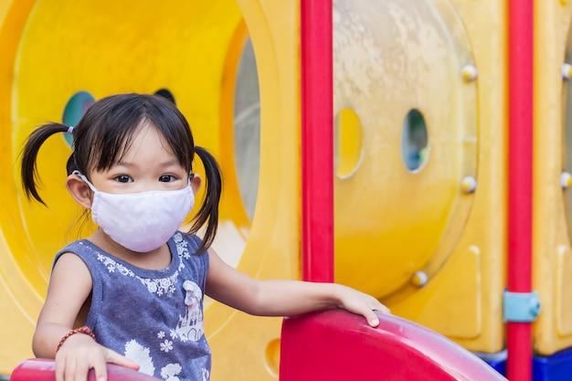 Szczęśliwa azjatycka dziewczyna dziecko uśmiecha się i nosi maskę z tkaniny.