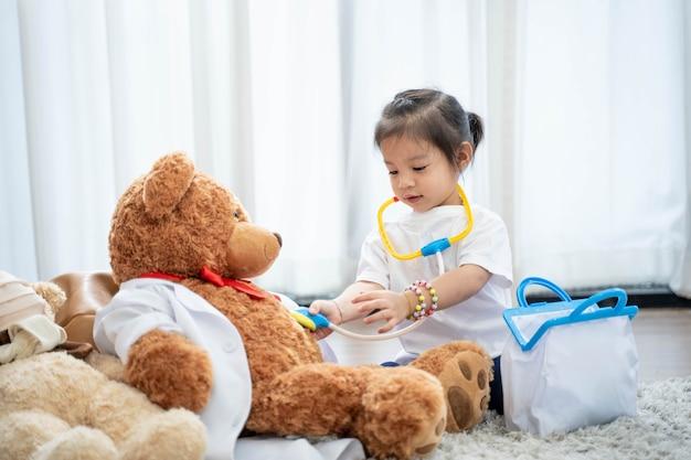 Szczęśliwa azjatycka dziewczyna gra lekarza lub pielęgniarkę słuchając stetoskopu do zabawki.