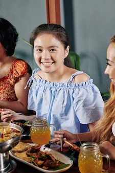 Szczęśliwa azjatycka dziewczyna je obiad