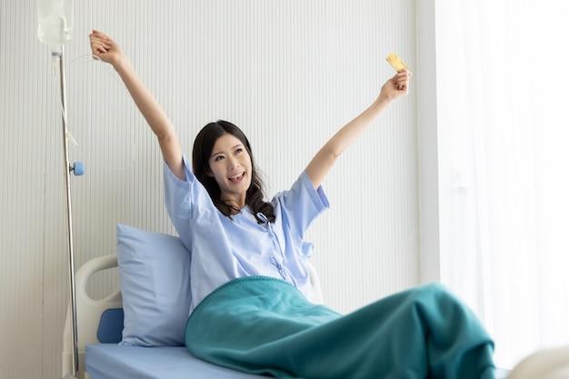 Szczęśliwa azjatycka dziewczyna na łóżku szpitalnym z kartą kredytową