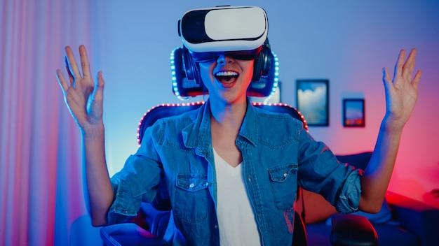 Szczęśliwa azjatycka dziewczyna nosi okulary wirtualnej rzeczywistości gogle zestaw słuchawkowy z wyrazem zaskoczenia