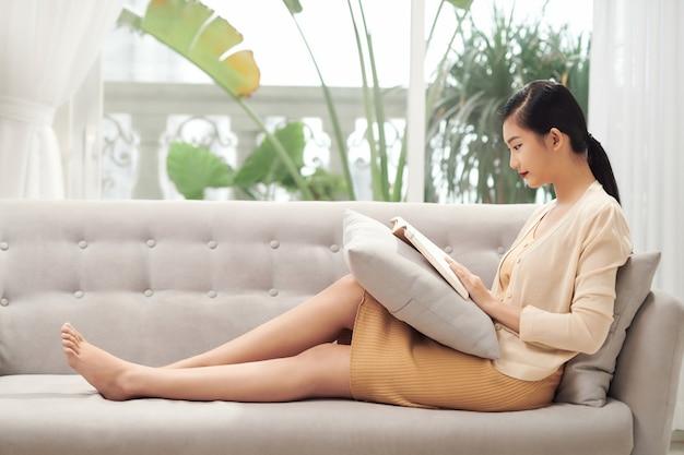 Szczęśliwa azjatycka dziewczyna odpoczywa na kanapie w salonie, czytając swoją ulubioną powieść