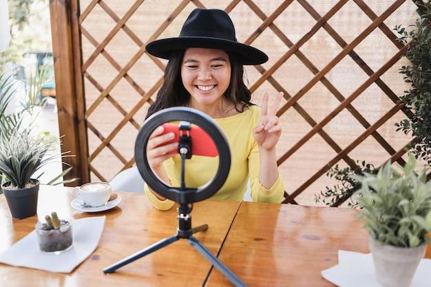 Szczęśliwa azjatycka dziewczyna przesyła strumieniowo online za pomocą kamery wpływowej i telefonu komórkowego w barze restauracyjnym - skup się na twarzy