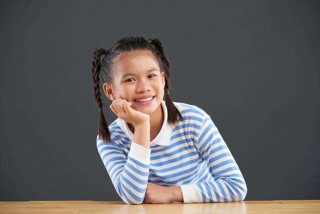 Szczęśliwa azjatycka dziewczyna siedzi z podbródkiem odpoczywa z jednej strony z warkoczami