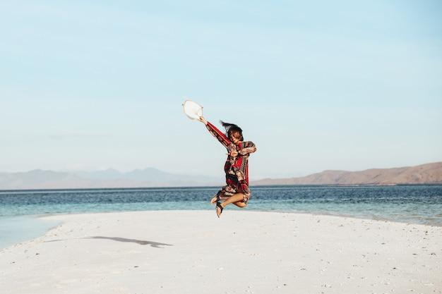 Szczęśliwa azjatycka dziewczyna skacze ciesząc się letnimi wakacjami na białej, piaszczystej plaży