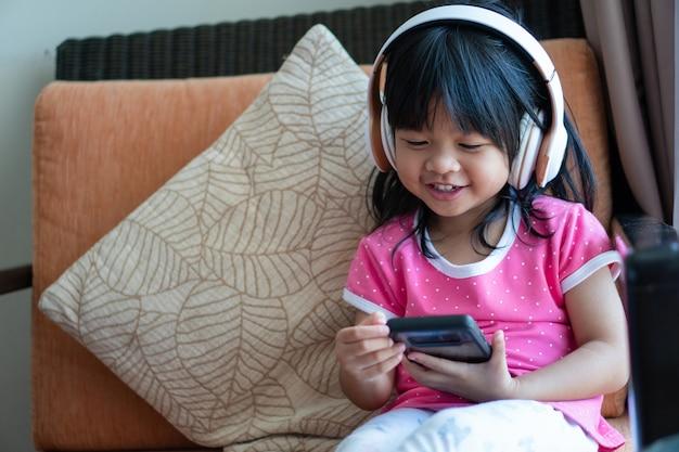 Szczęśliwa azjatycka dziewczyna uśmiecha się i cieszy się słucha muzykę w hełmofonach i trzyma smartphone na kanapa pokoju dziennym