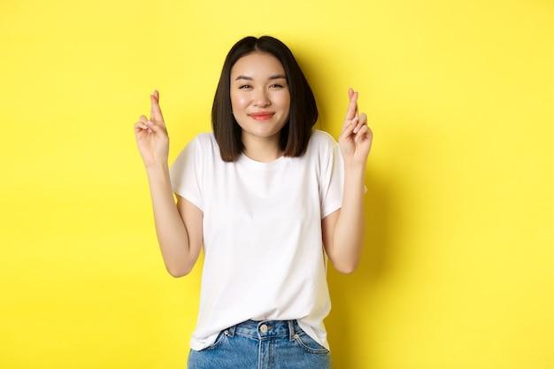 Szczęśliwa azjatycka dziewczyna uśmiecha się optymistycznie, czując się szczęśliwym, krzyżując palce i składając życzenia, patrząc w górę marzycielski, stojąc na żółtym tle.