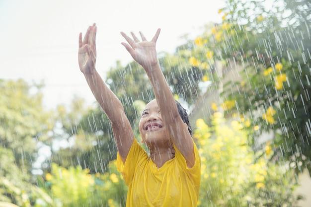 Szczęśliwa azjatycka dziewczynka bawi się z deszczem w słońcu