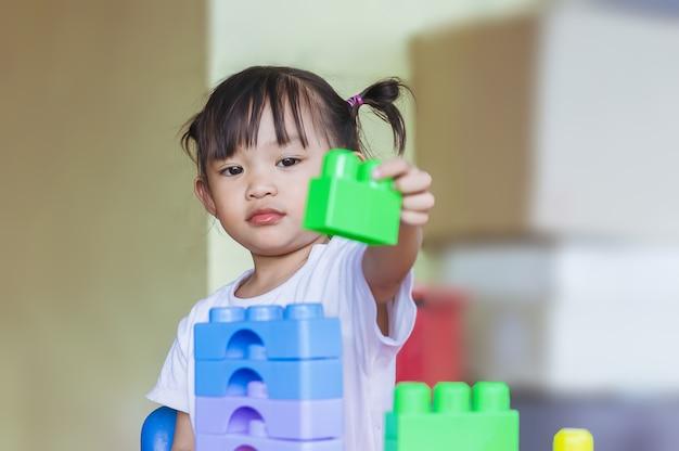 Szczęśliwa azjatycka dziewczynka bawiąca się plastikowymi zabawkami klockowymi nauka i edukacja