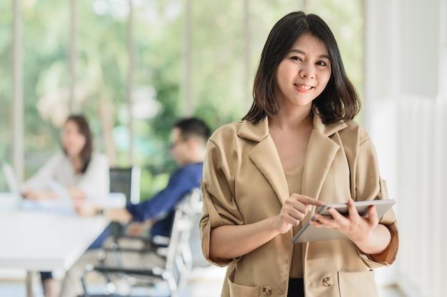 Szczęśliwa azjatycka kobieta biznesu za pomocą cyfrowego tabletu z kolegą w tle w sali konferencyjnej. koncepcja sukcesu lub osiągnięcia w biznesie
