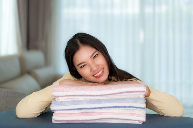 Szczęśliwa azjatycka kobieta gnieżdżąca się na czystych fałdowych ubraniach w domu.