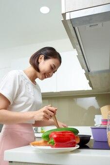 Szczęśliwa azjatycka kobieta gotowanie w kuchni.