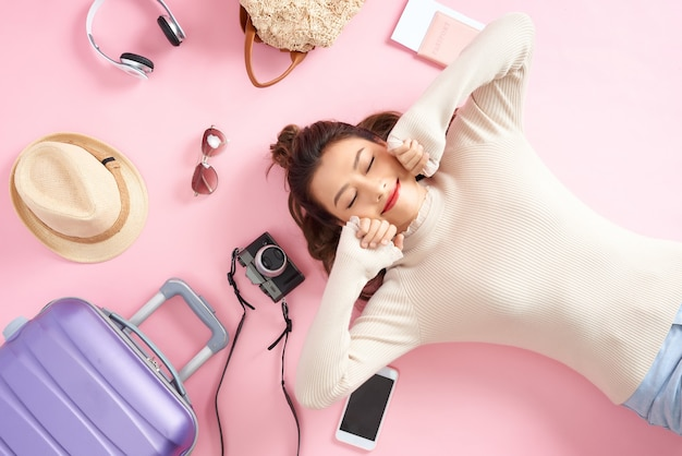 Szczęśliwa azjatycka kobieta leżąca na różowej podłodze z wieloma bagażami podróżnymi