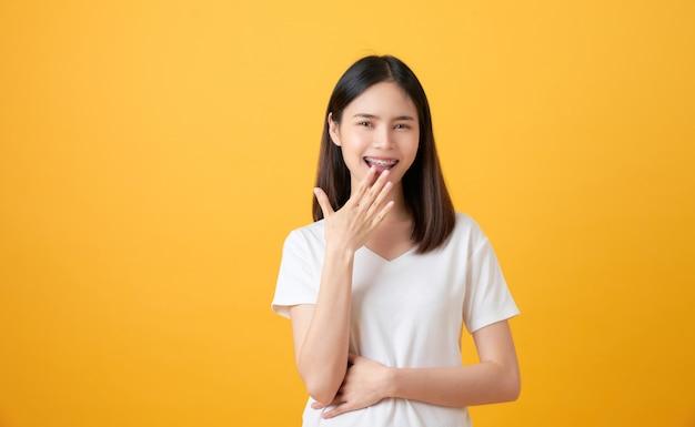 Szczęśliwa azjatycka kobieta na żółtym tle