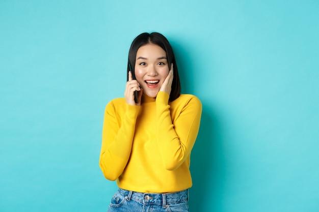 Szczęśliwa azjatycka kobieta otrzymuje ofertę na telefon, uśmiechając się podczas rozmowy na smartfonie, stojąc na niebieskim tle.