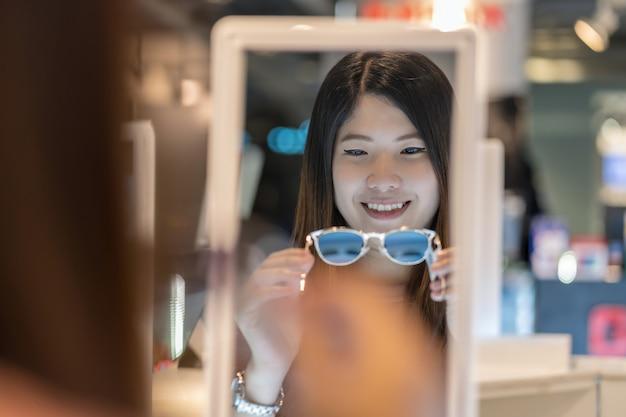 Szczęśliwa azjatycka kobieta patrzeje eyeglasses i wybiera w sklepu sklepie przy wydziałowym sklepem