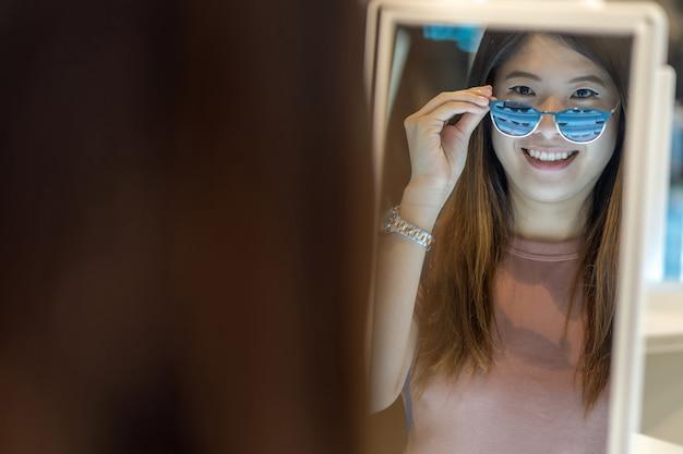 Szczęśliwa azjatycka kobieta patrzeje eyeglasses w sklepu sklepie i wybiera przy wydziałowym sklepem