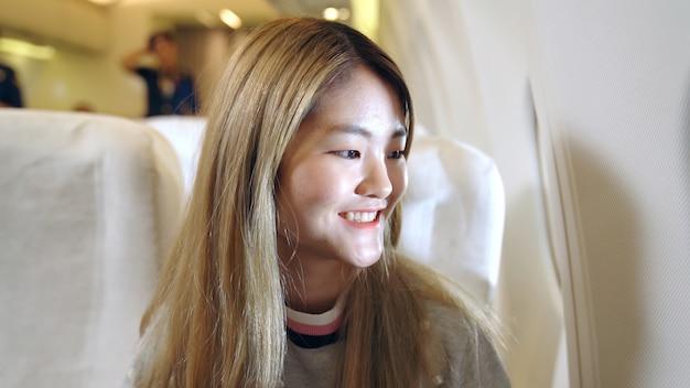 Szczęśliwa azjatycka kobieta podróżuje samolotem