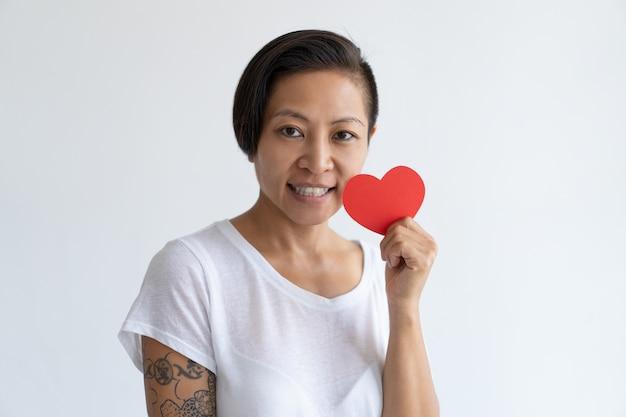 Szczęśliwa azjatycka kobieta pozuje z papierowym sercem