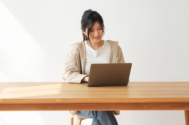 Szczęśliwa azjatycka kobieta pracująca w domu