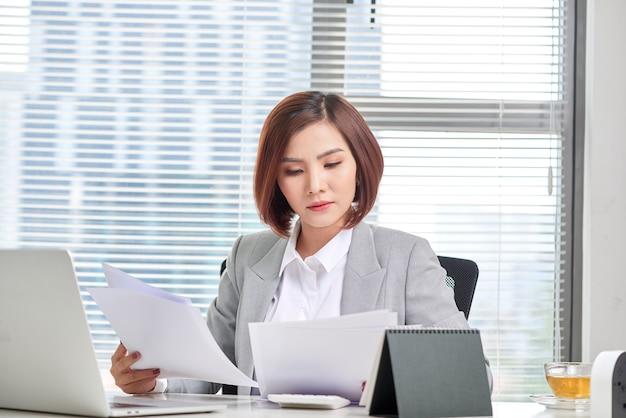 Szczęśliwa Azjatycka Kobieta Pracuje W Biurze. Kobieta Przechodzi Przez Papierkową Robotę W Miejscu Pracy. Premium Zdjęcia