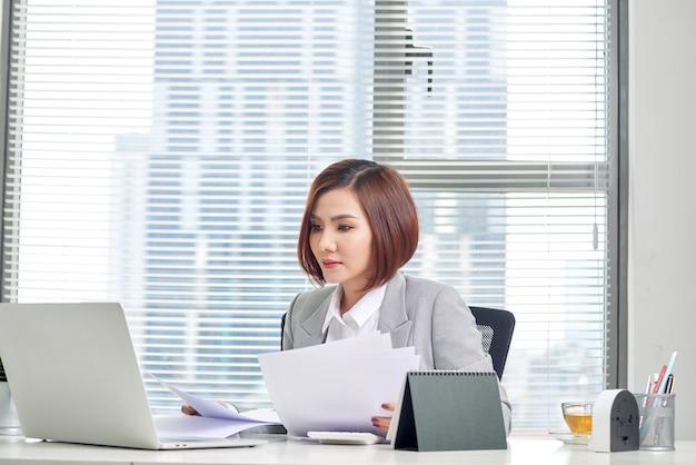 Szczęśliwa azjatycka kobieta pracuje w biurze. kobieta przechodzi przez papierkową robotę w miejscu pracy.