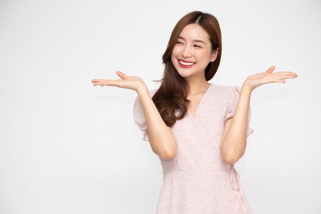 Szczęśliwa azjatycka kobieta przedstawiająca otwartą dłoń z miejscem na kopię produktu na białym tle
