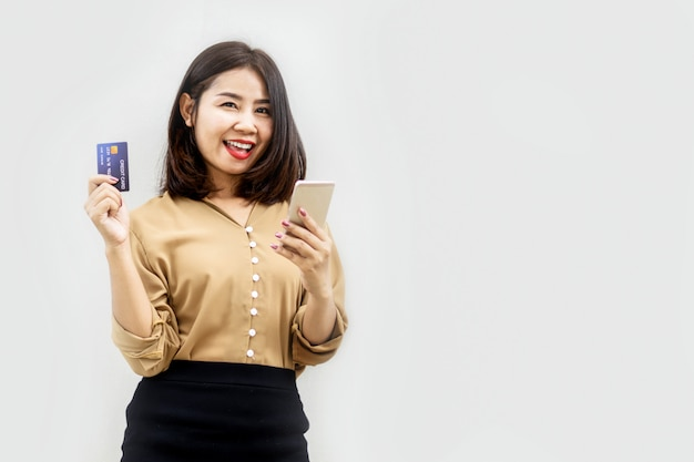 Szczęśliwa azjatycka kobieta robi zakupy online z kartą kredytową