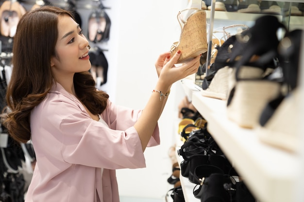 Szczęśliwa azjatycka kobieta robi zakupy w buta sklepie z cieszyć się podekscytowany o gorącej sprzedaży końcówce sezonu w centrum handlowym