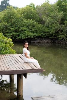 Szczęśliwa azjatycka kobieta siedzi na drewnianym moście nad kanałem zielonym w pobliżu lasu namorzynowego w koh phayam, ranong, tajlandia