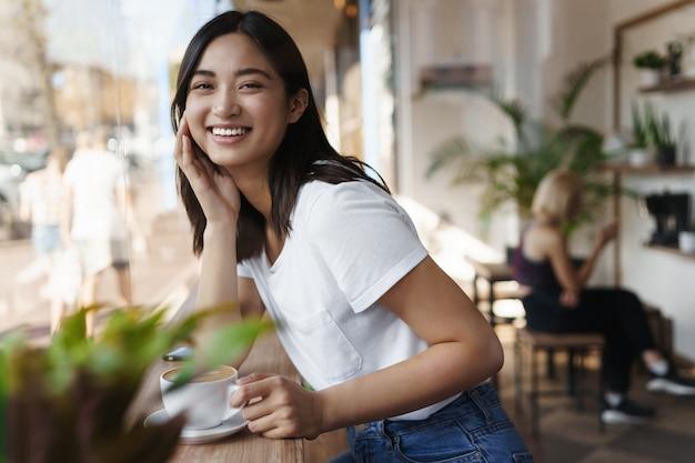 Szczęśliwa azjatycka kobieta siedzi w restauracji w pobliżu okna i uśmiecha się do kamery.