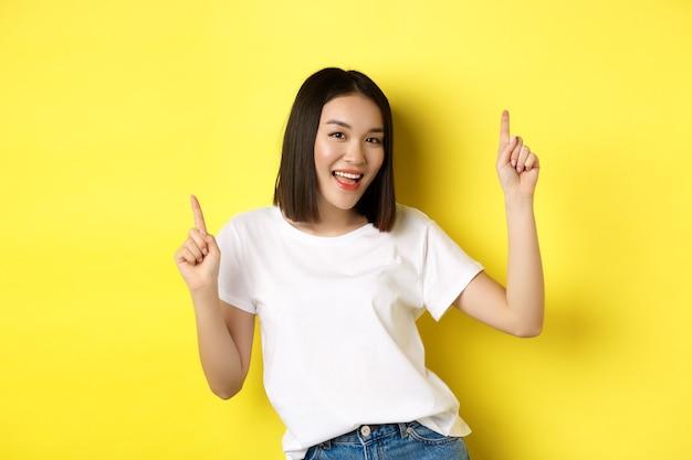 Szczęśliwa azjatycka kobieta tańczy i zabawy, pozowanie w białej koszulce na żółtym tle.