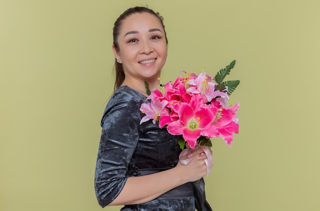 Szczęśliwa azjatycka kobieta trzyma bukiet kwiatów uśmiechnięta wesoło świętuje międzynarodowy dzień kobiet stojąc nad zieloną ścianą