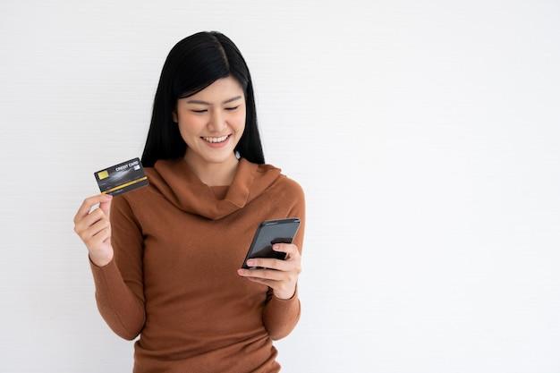 Szczęśliwa azjatycka kobieta trzyma kartę kredytową i smartfon dla bankowości mobilnej w internecie.