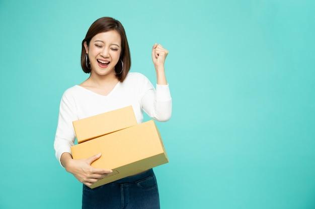 Szczęśliwa azjatycka kobieta trzyma pakiet paczek pudełko