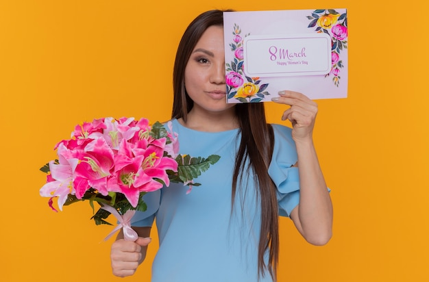 Szczęśliwa azjatycka kobieta trzyma powitanie obejmujące jedno oko kartą trzyma bukiet kwiatów z okazji międzynarodowego dnia kobiet marca